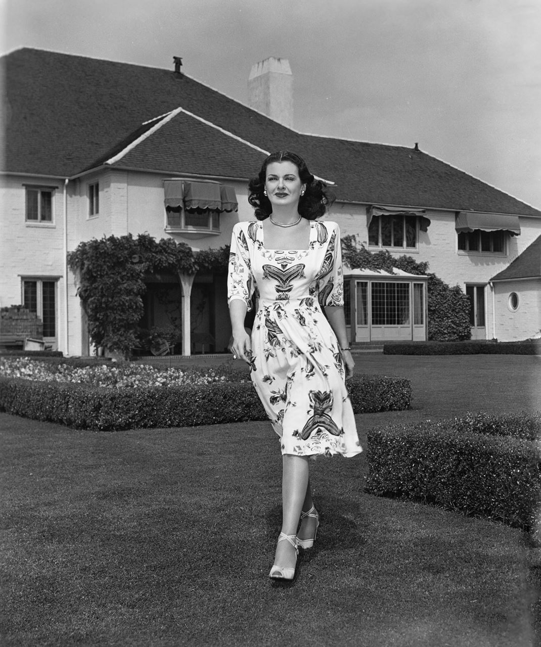 The photo shows film star Joan Bennett strolling through the Tomson-designed garden of her Wallace Neff estate in Holmby Hills. Photo courtesy Marc Wanamaker/Bison Archives